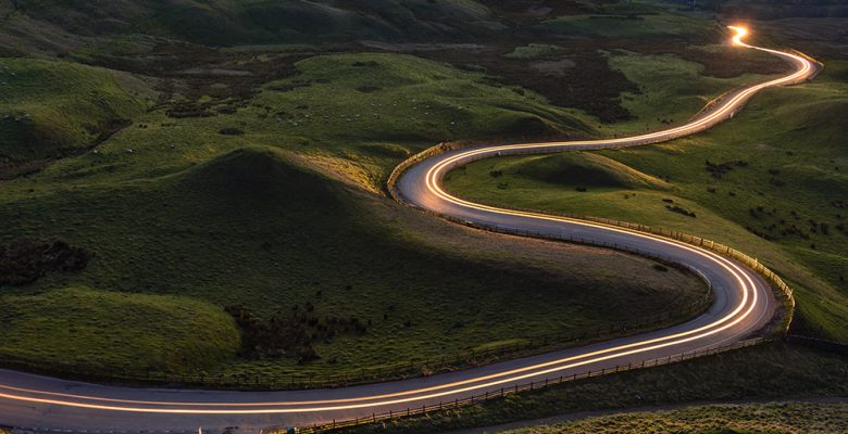 Winding curvy rural road with light trail from headlights leadin
