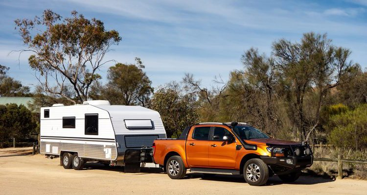 Off road pickup car with air intakes and a white caravan trailer