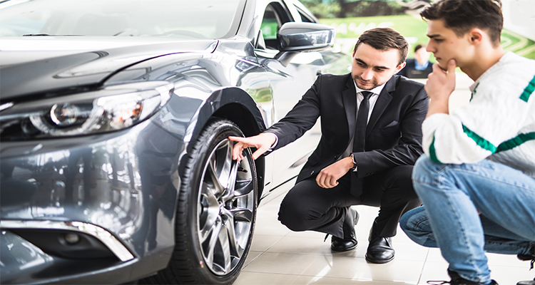 Young car salesman showing the advantages of the car to the customer and tires.